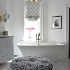 white bathroom with storage cabinet and freestanding bathtub